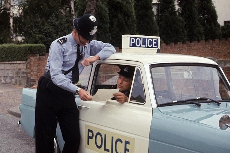 A policeman talks to the driver of a Ford Anglia police panda car in the early 1970s. - Credit: BBC