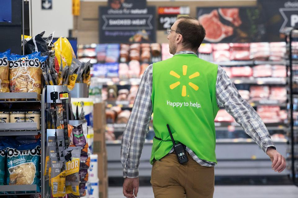A Walmart associate works at a Walmart Neighborhood Market, Wednesday, April 24, 2019, in Levittown, N.Y.  Inside one of Walmart's busiest Neighborhood Market stores, thousands of cameras suspended from the ceilings track when products are running low or when produce or meat start to lose their freshness. The technology is one of several features of a living lab that officially opens inside this store on Thursday. (AP Photo/Mark Lennihan)