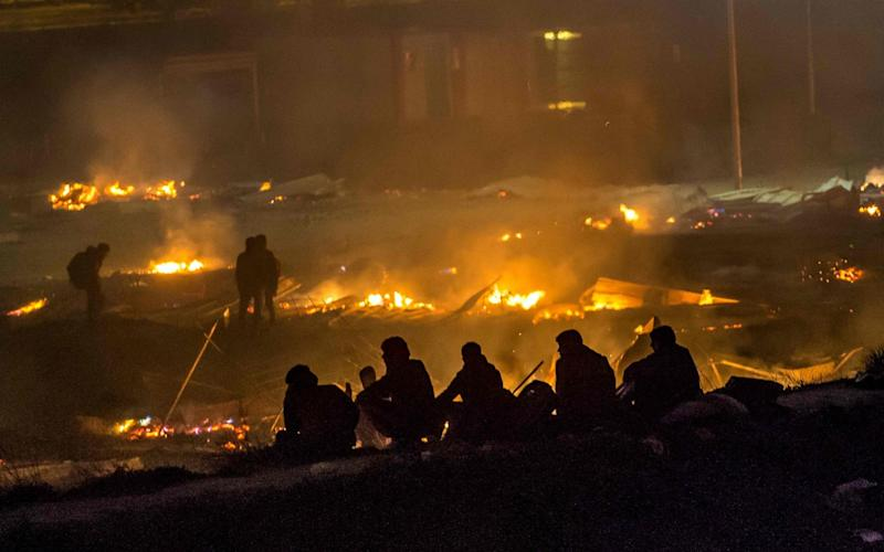 Migrants evacuate as a huge fire blazes through the Grande Synthe camp - Credit: PHILIPPE HUGUEN/AFP