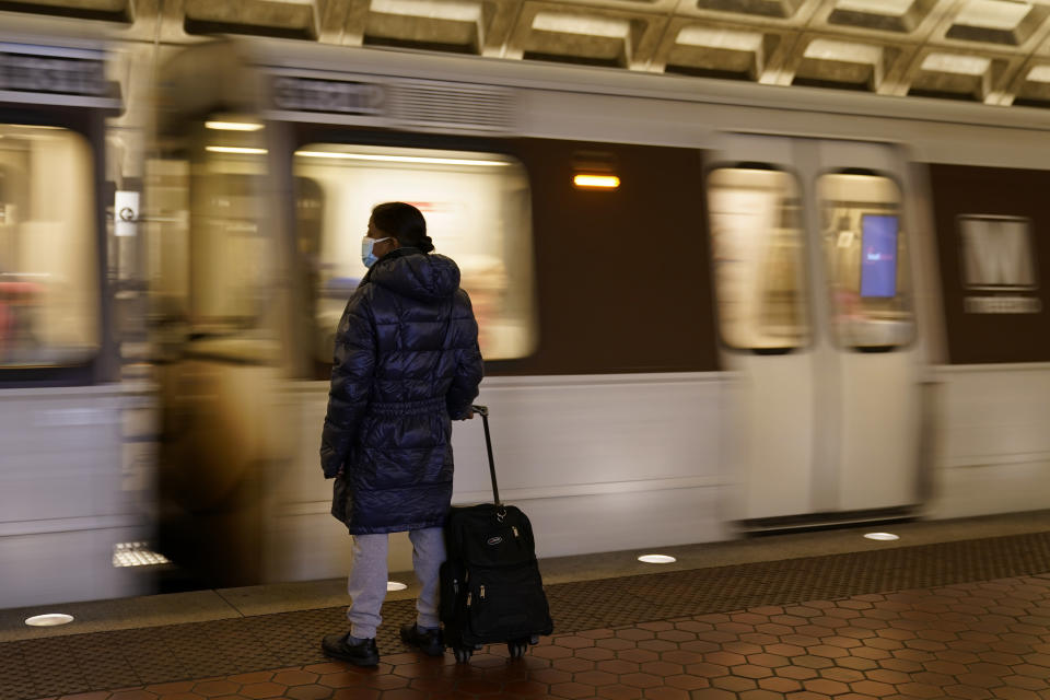 A woman waits to board a train as it arrives at Metro Center station, Friday, April 23, 2021, in Washington. As President Joe Biden urges more federal spending for public transportation, transit agencies decimated by COVID-19 are struggling with a new uncertainty: how to win passengers back. (AP Photo/Patrick Semansky)