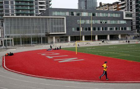 Students congregate on the playing field of the North Toronto Collegiate Institute