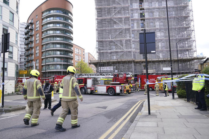 Firefighters at the scene in New Providence Wharf in London, Friday, May 7, 2021. Firefighters have tacked a blaze in a London apartment tower that has cladding similar to that used on a building where 72 people died in 2017. London Fire Brigade said about 125 firefighters tackled a fire on Friday that spread to three floors of a 19-story building in the city's docklands. (Yui Mok/PA via AP)