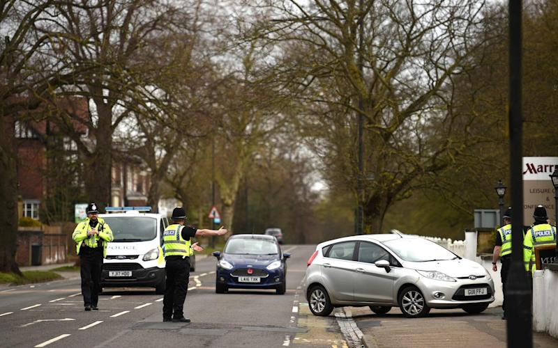 Police officers from North Yorkshire Police stop motorists in cars to check that their travel is 'essential' - Oli Scarff/AFP