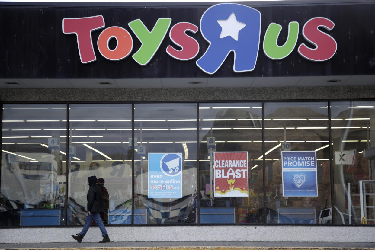 FILE - In this Jan. 24, 2018, file photo, a person walks near the entrance to a Toys R Us store, in Wayne, N.J. A group of investors is planning a potential comeback for Geoffrey the giraffe and his crew. Investors that control the assets of the company say they now see a better chance of a return on investment by potentially reviving the toy chain, rather than selling it off for parts. (AP Photo/Julio Cortez, File)