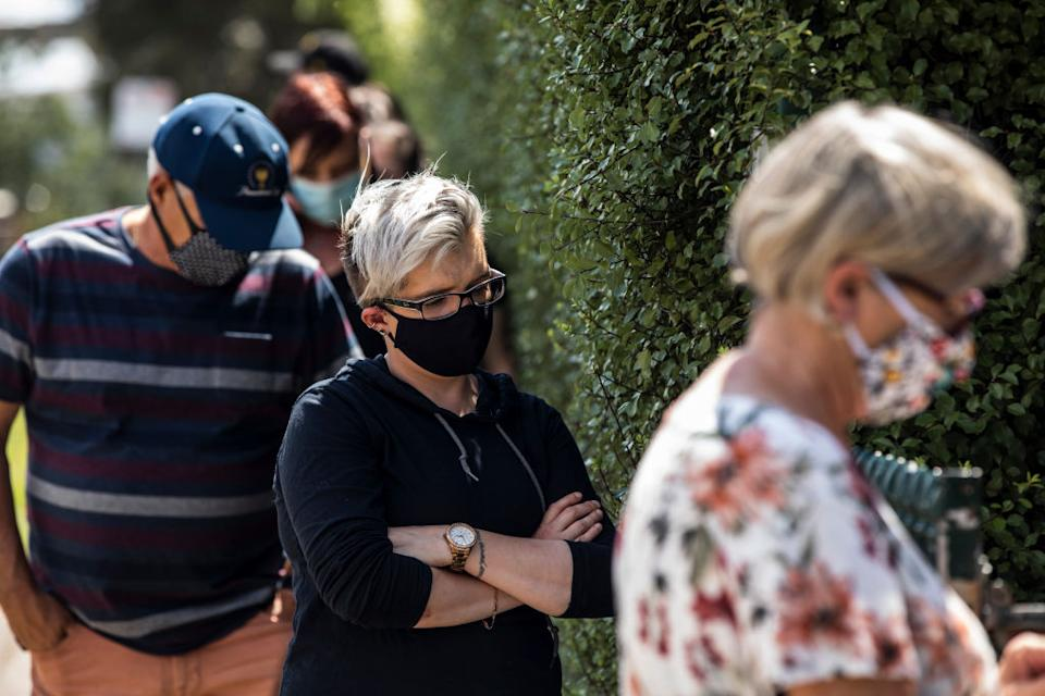 A woman wears a face mask while she waits for a Covid-19 test outside the Sunbury Respiratory Clinic in Melbourne. Source: Getty Images