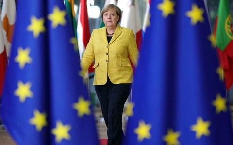 German Chancellor Angela Merkel walks into an EU summit at the Europa building in Brussels through different nations' flags with the EU flag on both her left and right hand side, on Thursday, Dec. 14, 2017, wearing a yellow suit jacket and black trousers - Credit: Oliver Matthys/AP