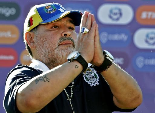 Maradona gestures to supporters as he leaves the field after a Superliga match against Estudiantes