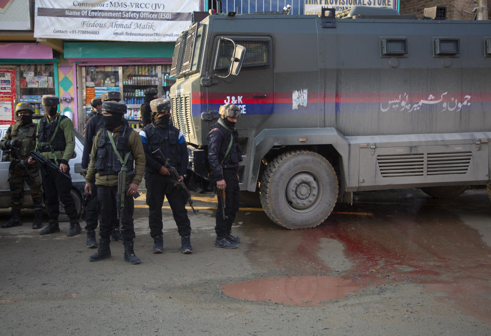 Indian security officers stand at the site of an attack on the outskirts of Srinagar, Indian controlled Kashmir, Thursday, Nov. 26, 2020. Anti-India rebels in Indian-controlled Kashmir Thursday killed two soldiers in an attack in the disputed region's main city, the Indian army said.(AP Photo/Mukhtar Khan)