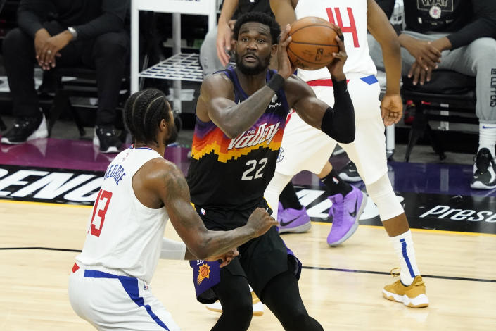 Phoenix Suns center Deandre Ayton (22) shoots as Los Angeles Clippers guard Paul George (13) defends during the first half of game 5 of the NBA basketball Western Conference Finals, Monday, June 28, 2021, in Phoenix. (AP Photo/Matt York)