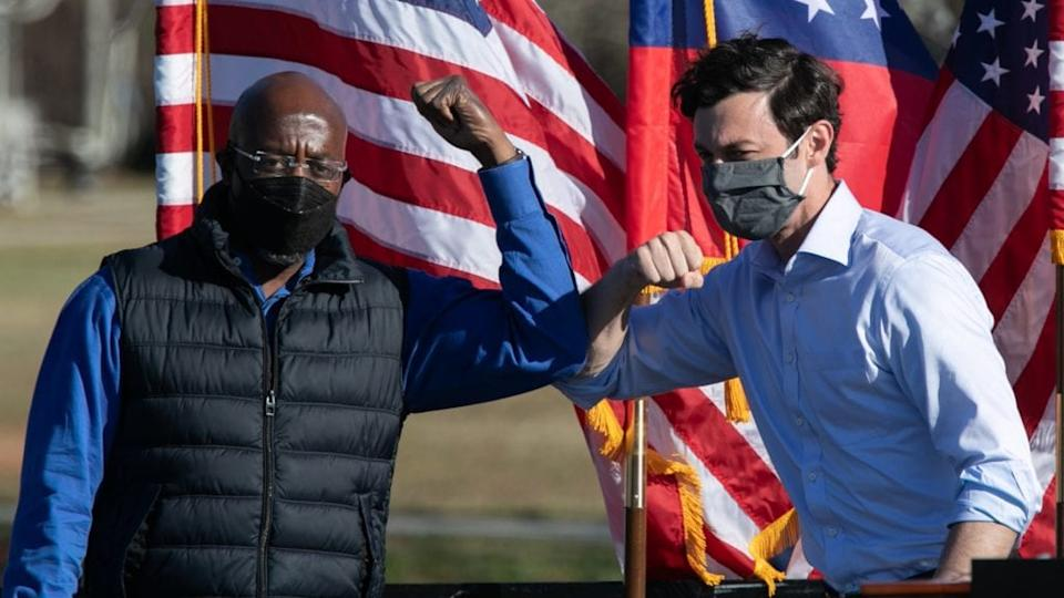 Democratic U.S. Senate candidates Raphael Warnock (left) and Jon Ossoff bump elbows during a Dec. 5 outdoor drive-in rally in Conyers, Georgia. (Photo by Jessica McGowan/Getty Images)