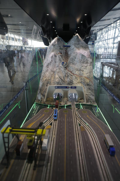 In this Sept. 12, 2012 photo taken through glass, a toy train emerges from a tunnel inside a miniature model of the proposed Aconcagua Bi-Oceanico Corridor, on display at the airport in Santiago, Chile. Two of South America's leading economies are neighbors but might as well be worlds apart, separated by a mountain wall with only one major land crossing that gets snowed in for up to two months every winter. An ambitious effort to build a private railway under Andean peaks aims to end the bottleneck. (AP Photo/Eduardo Di Baia)