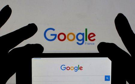 File photo of a woman holding her smart phone which displays the Google home page, in this picture illustration