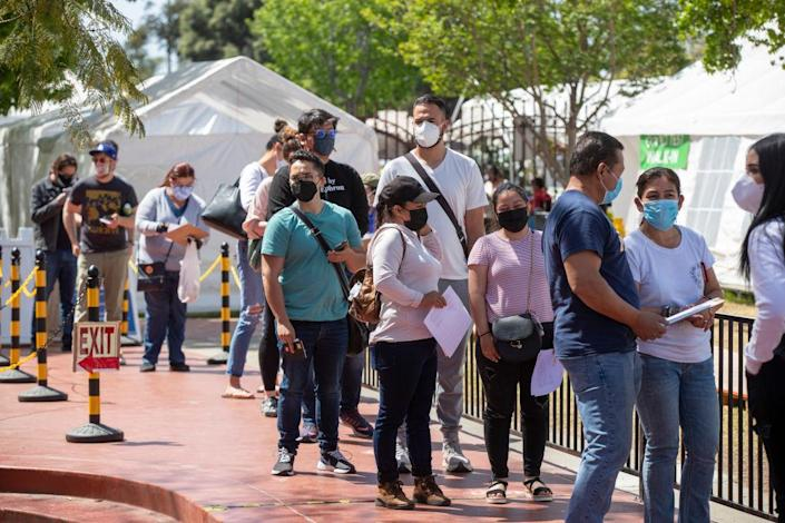 People wait in line to receive the COVID-19 Vaccination at Kedren Health on April 15, a day that vaccines were made available to all people 16+ in Los Angeles. (Allen J. Schaben / Los Angeles Times via Getty Images)