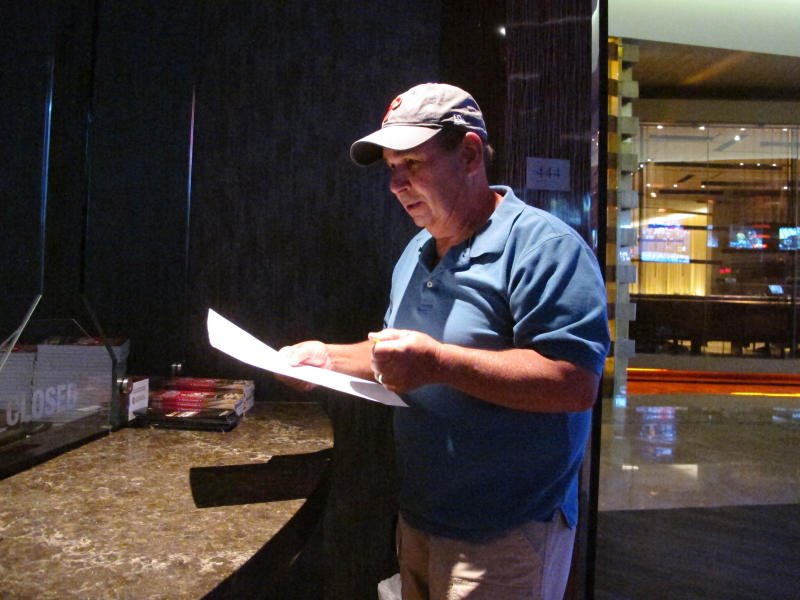 In this Sept. 4, 2019 photo, Andy Lanni of Oceanview, N.J. checks the odds at the sports book in the Borgata casino in Atlantic City, N.J. As the second NFL season begins following a U.S. Supreme Court decision clearing the way for legal sports betting, the industry is growing larger and ever-more mobile in the U.S. (AP Photo/Wayne Parry)