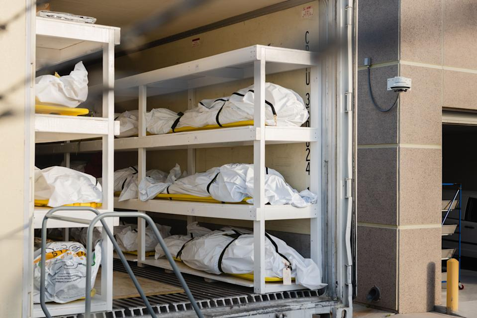 Bodies wrapped in plastic line the walls inside a refrigerated trailer used as a mobile morgue by the El Paso County Medical Examiner's office. Source: Getty