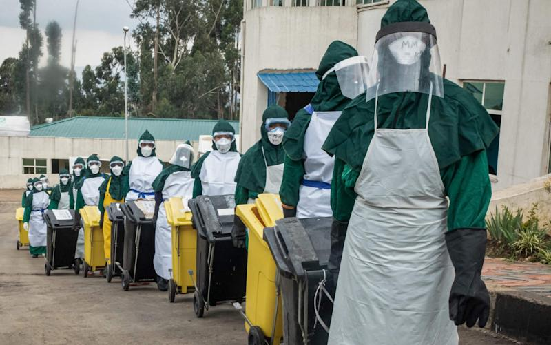 Cleaning staff in personal protective equipment (PPE) carry lidded trash boxes in a line to minimize contamination after collecting PPEs used by doctors who treated patients infected with the COVID-19 novel coronavirus in the intensive care unit (ICU) at Saint Petros Hospital in Addis Ababa, - AFP