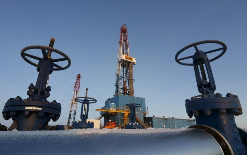 An oil pipe is seen in front of a drilling rig at a Lukoil-owned oil field outside the West Siberian city of Kogalym