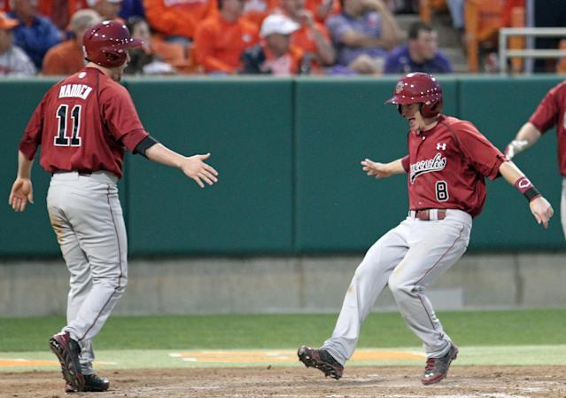 South Carolina's Marcus Mooney, right, celebrates with Zack Madden after they scored the winning runs in the ninth inning to defeat Clemson 5-3 in an NCAA college baseball game on Sunday, March 2, 2014, in Clemson, S.C. (AP Photo/Anderson Independent-Mail, Mark Crammer)