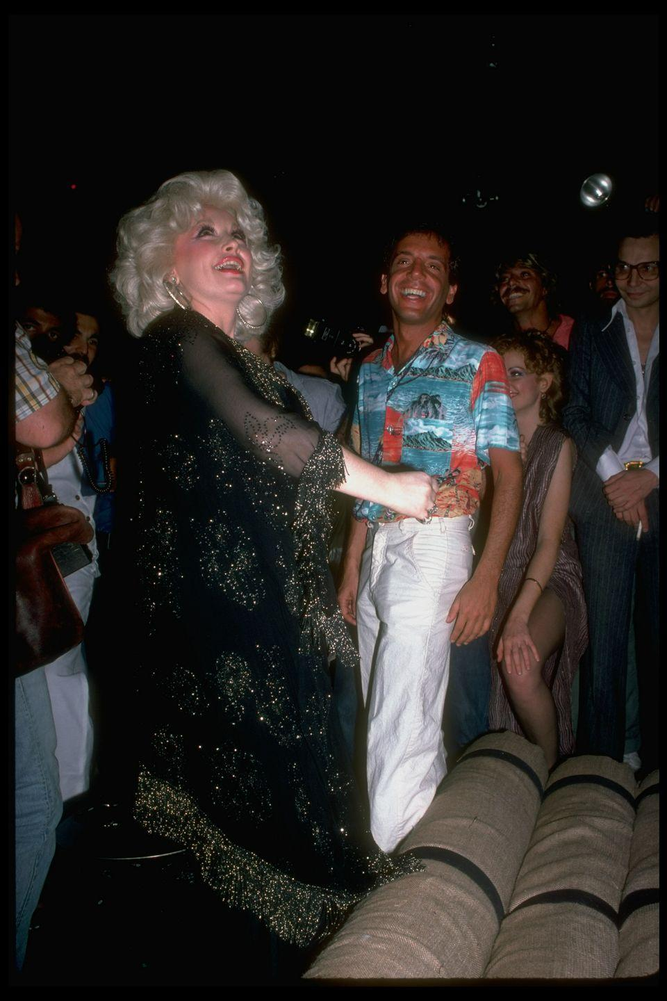 <p>Dolly Parton stuns in her typical fashion as she dances with Studio 54 owner, Steve Rubell, at the New York City nightclub in 1978.</p>