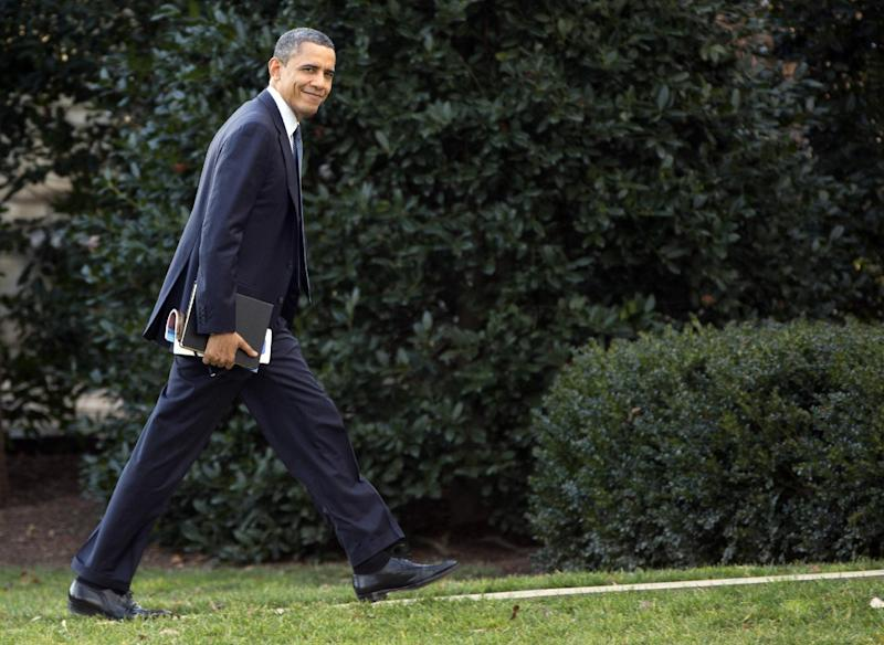 President Barack Obama looks to the media as he walks to the Oval Office of the White House as he returns from greeting members of the staff, Tuesday, Dec. 18, 2012, in Washington. (AP Photo/Carolyn Kaster)