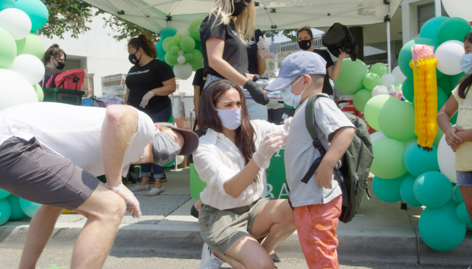 """<p>When Meghan volunteered with the non-profit Baby2Baby, handing out supplies ahead of the new school year, she wore a cloth mask <a href=""""https://royaljellyharlem.com/"""" rel=""""nofollow noopener"""" target=""""_blank"""" data-ylk=""""slk:Royal Jelly"""" class=""""link rapid-noclick-resp"""">Royal Jelly</a>, a New York City based, Black-owned company.</p><p><a class=""""link rapid-noclick-resp"""" href=""""https://royaljellyharlem.com/"""" rel=""""nofollow noopener"""" target=""""_blank"""" data-ylk=""""slk:Shop Here"""">Shop Here</a></p>"""