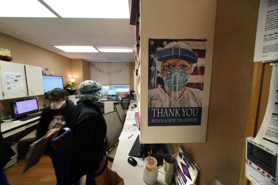 FILE - In this Aug. 18, 2021, file photo, a poster honoring medical and frontline workers, hangs on a nursing station of an intensive care unit, at the Willis-Knighton Medical Center in Shreveport, La. The COVID-19 pandemic has created a nurse staffing crisis that is forcing many U.S. hospitals to pay top dollar to get the help they need to handle the crush of patients this summer. (AP Photo/Gerald Herbert, File)