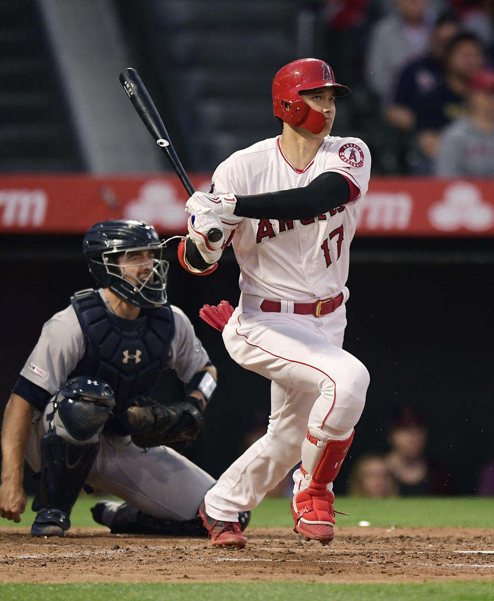 Los Angeles Angels' Shohei Ohtani watches his groundout in front of Seattle Mariners catcher Tom Murphy during the third inning of a baseball game Friday, June 7, 2019, in Anaheim, Calif. (AP Photo/Mark J. Terrill)