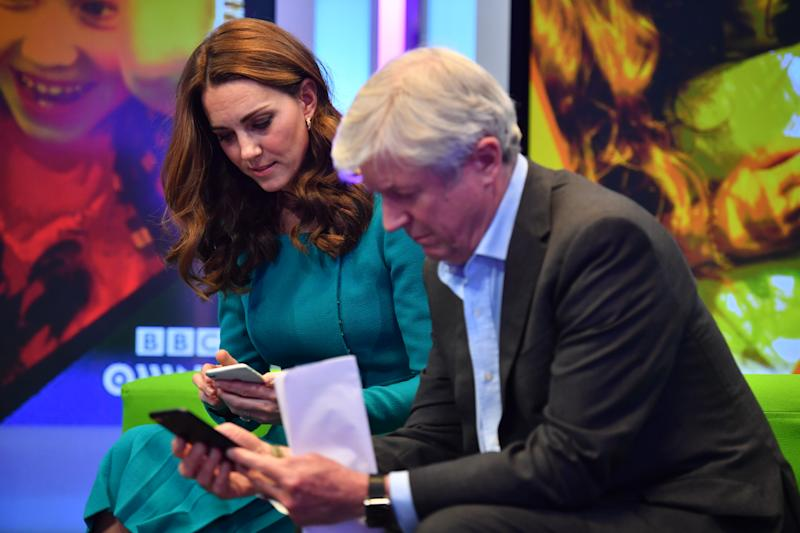 LONDON, ENGLAND - NOVEMBER 15: Catherine, Duchess of Cambridge, (L) sits with Director-General of the BBC Tony Hall (R) as they try out an App designed to combat online bullying during a visit BBC Broadcasting House on November 15, 2018 in London, England. The Royal couple came to view the work the broadcaster is doing as a member of The Duke's Taskforce on the Prevention of Cyberbullying. (Photo by Ben Stansall - WPA Pool/Getty Images)