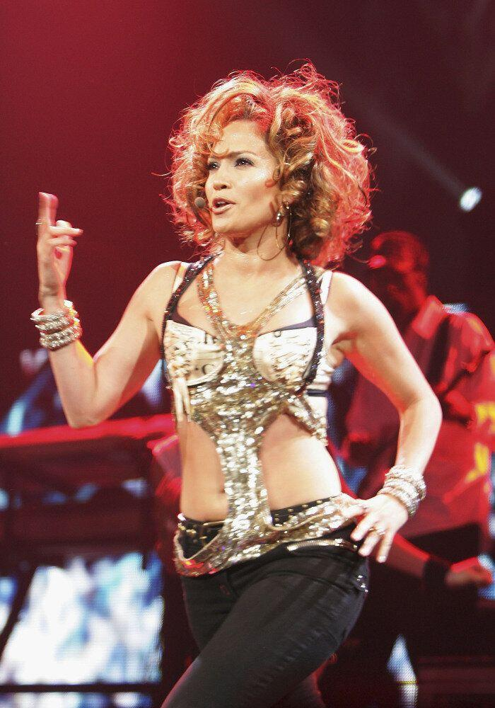 Jennifer Lopez performs wearing a cut out gold top and black trousers with her hair short and curly.
