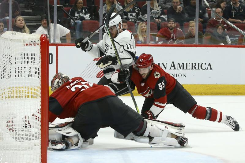 Arizona Coyotes goaltender Antti Raanta, left, makes a save as Coyotes defenseman Jason Demers (55) muscles Los Angeles Kings center Anze Kopitar (11) during the third period of an NHL hockey game, Monday, Nov. 18, 2019, in Glendale, Ariz. The Coyotes defeated the Kings 3-0. (AP Photo/Ross D. Franklin)