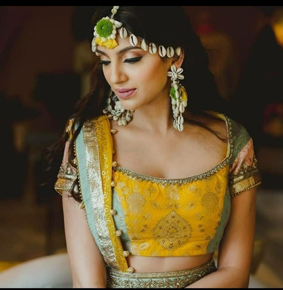 While Miheeka was a sight to behold at Haldi in a yellow and golden lehenga which is well complemented with chunky jewellery made with cowrie shells.