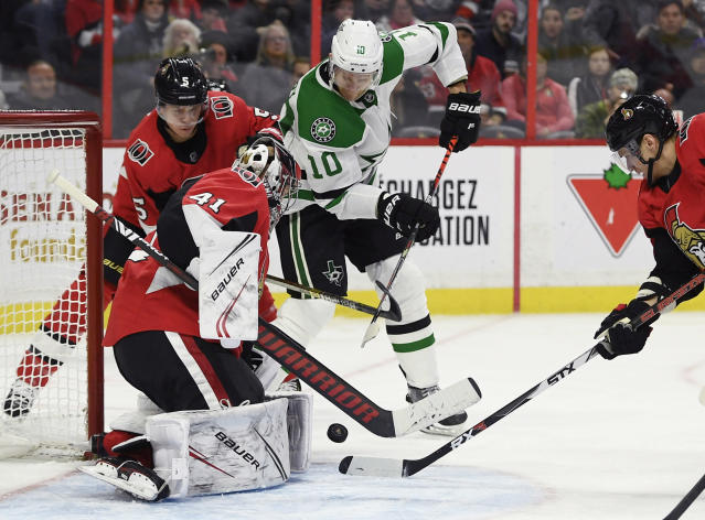 Ottawa Senators goaltender Craig Anderson (41) and defenseman Mike Reilly (5) keep the puck from Dallas Stars right wing Corey Perry (10) during the second period of an NHL hockey game Sunday, Feb. 16, 2020, in Ottawa, Ontario. (Justin Tang/The Canadian Press via AP)