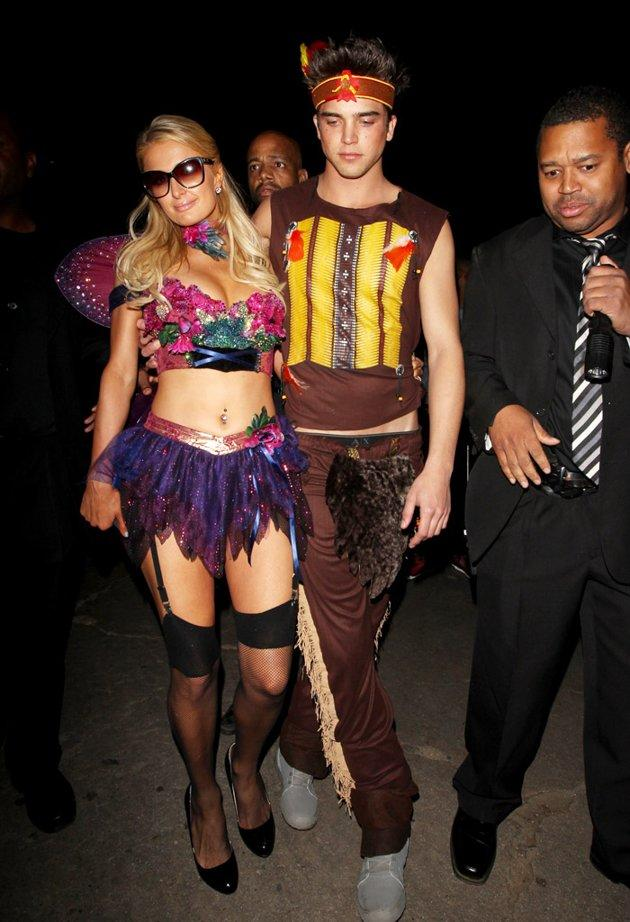 "Paris Hilton sported a skimpy fairy outfit while her boyfriend River Viiperi dressed as an Indian for the party at the Playboy Mansion. The costumes were their second of the weekend since they dressed as Alice from ""Alice in Wonderland"" and the Mad Hatter on Friday for a private bash in Beverly Hills. (10/28/2012)"
