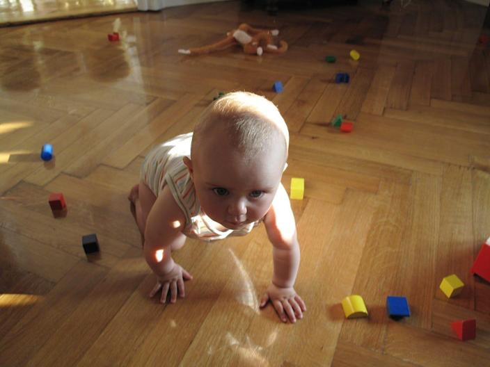 A baby crawling on a floor covered in toys.