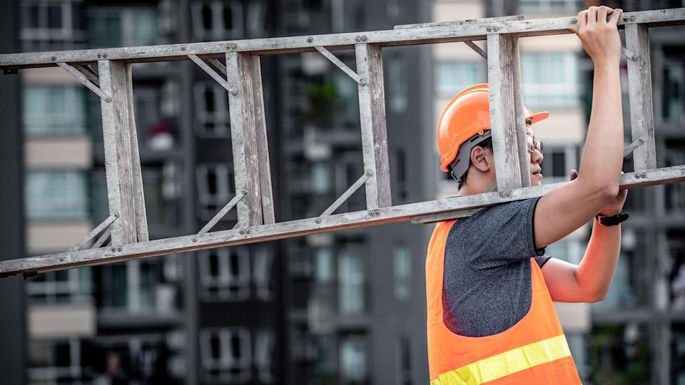 Young Asian maintenance worker with orange safety helmet and vest carrying aluminium step ladder at construction site.
