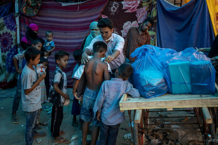A Rohingya activist distributes new clothes among refugees at a refugee camp alongside the banks of the Yamuna River in the southeastern borders of New Delhi, sprawling Indian capital, July 1, 2021. Millions of refugees living in crowded camps are waiting for their COVID-19 vaccines. For months, the World Health Organization urged countries to prioritize immunizing refugees, placing them in the second priority group for at-risk people, alongside those with serious health conditions. (AP Photo/Altaf Qadri)