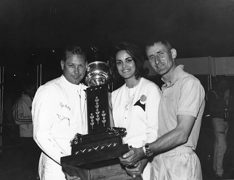 DAYTONA BEACH, FL - FEBRUARY 28, 1965: Race winners Lloyd Ruby and Ken Miles are joined in victory lane by the reigning Miss Universe, Corinna Tsopei of Greece, following their win in the Daytona Continental at Daytona International Speedway. (Photo by ISC Images & Archives via Getty Images)