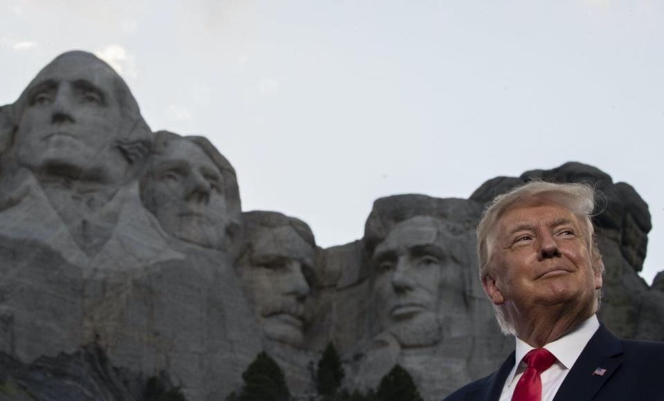"""<span class=""""caption"""">In this July 2020 photo, former president Donald Trump stands at the Mount Rushmore National Memorial in South Dakota. </span> <span class=""""attribution""""><span class=""""source""""> (AP Photo/Alex Brandon)</span></span>"""
