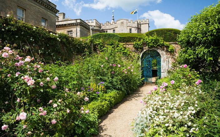 A glimpse of Rousham House from within the walled garden, with its wide herbaceous borders and gravel path - Andrew Baskott / Alamy Stock Photo