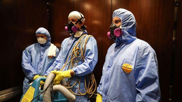PHOTO: Maryland Cleaning and Abatement Services employees Graham Sevy (L), Bob Wiglesworth, (C) and Alec Pine (R) ride in an elevator before preforming a preventative fogging and damp wipe treatment on March 21, 2020 in Hunt Valley, Maryland. (Rob Carr/Getty Images)