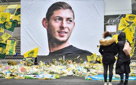 Yellow flowers displayed in front of a portrait of Emiliano Sala at the Beauvoir stadium in Nantes - Credit: afp