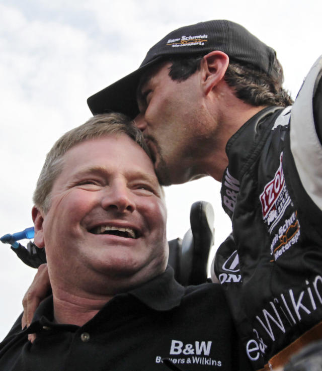 "FILE - In this May 21, 2011, file photo, Alex Tagliani, top, of Canada, kisses car owner Sam Schmidt after winning the pole on the opening day of qualifications for the Indianapolis 500 auto race at Indianapolis Motor Speedway in Indianapolis. Schmidt was watching his team tuneup a pair of engines, the roar was relentless, and the man had to lean in close and shout in Schmidt's ear to be heard. Thank you, the man said over and over, never expanding upon his gratitude. He tried to shake Schmidt's hand, awkwardly just patted it, thanked him again and backed away. ""Happens about 10 times a weekend,"" Schmidt said. ""You never know what the connection is.""(AP Photo/AJ Mast, File)"