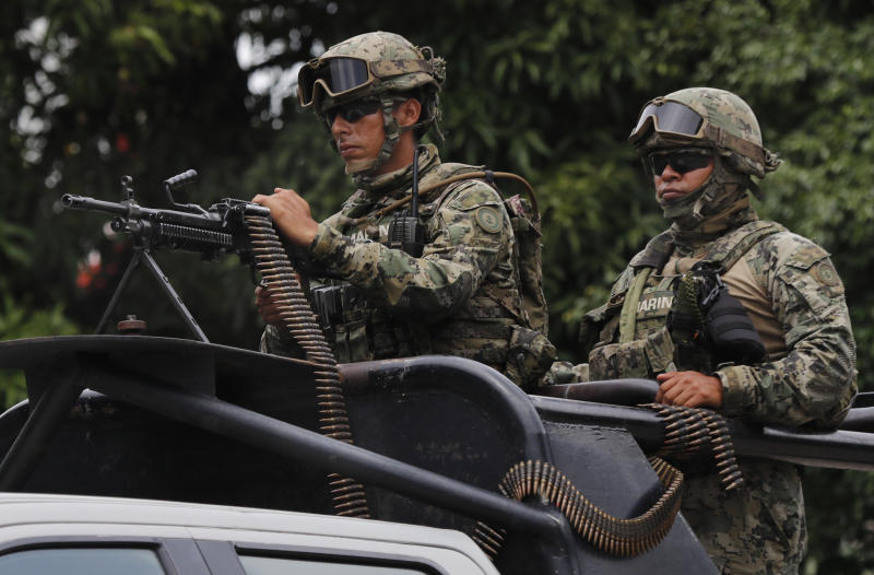 Mexican marines ride in the back of a pick up truck as they escort the caravan carrying Mexico's Minister of Defense, in Tapachula, Mexico, Tuesday, June 11, 2019. Mexican officials say they are beginning deployment of 6,000 National Guard troops for immigration enforcement, an accelerated commitment made as part of an agreement with the United States last week to head off threatened U.S. tariffs on imports from Mexico. (AP Photo/Marco Ugarte