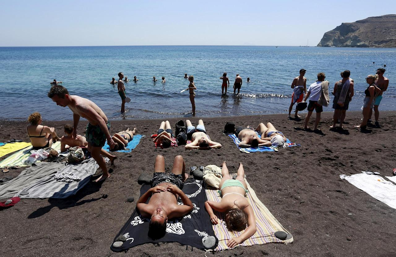 Tourists sunbathe on the Red Beach on the Greek island of Santorini, Greece, July 2, 2015.  REUTERS/Cathal McNaughton/Files