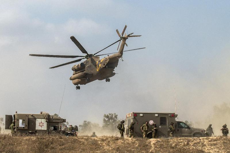 Israeli soldiers evacuate their wounded comrades at an army deployment area near Israel's border with the Gaza Strip on July 23, 2014