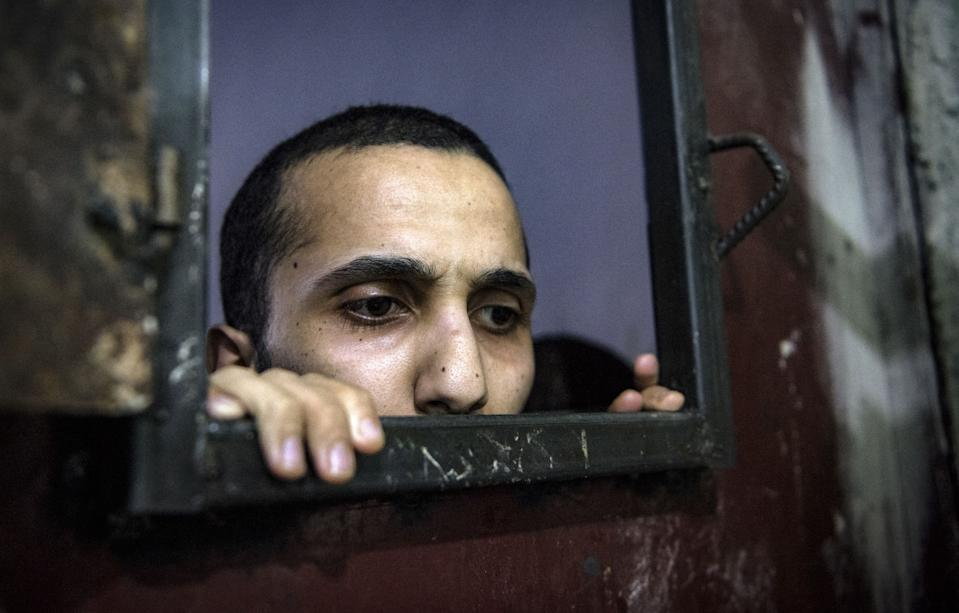 A prisoner looks out of the opening of a cell (Picture: AFP)