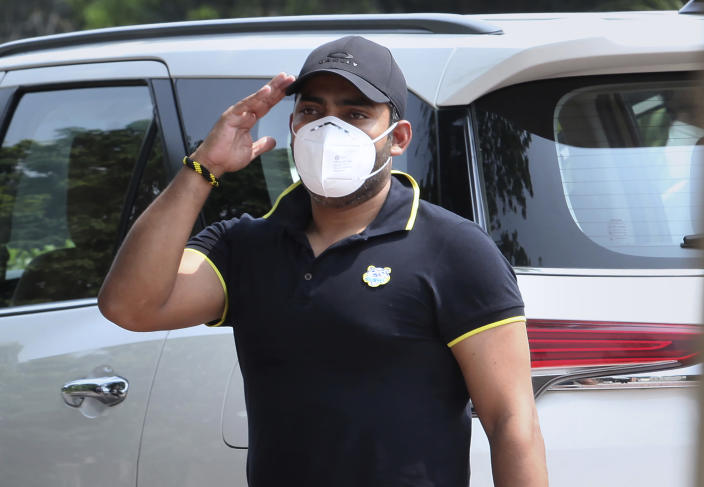 Pakistani cricketer Umar Akmal salutes to media while he arrives at the Pakistan Cricket Board office in Lahore, Pakistan, Wednesday, July 29, 2020. An independent adjudicator has halved batsman Akmal's ban to 18 months for failing to report corrupt approaches before this year's Pakistan Super League. (AP Photo/K.M. Chaudhry)