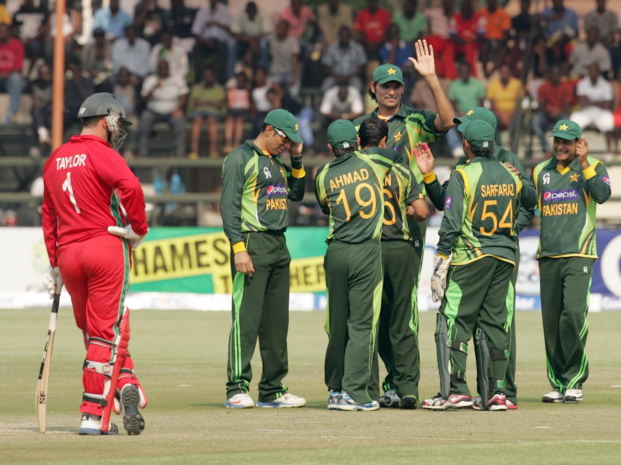Zimbabwe captain Brendan Taylor (L) watches Pakistan players celebrate a wicket on August 31, 2013 during the third and final one-day international at the Harare Sports Club. AFP PHOTO / JEKESAI NJIKIZANA        (Photo credit should read JEKESAI NJIKIZANA/AFP/Getty Images)