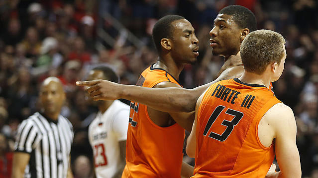 Oklahoma State's Markel Brown(22) and Phil Forte(13) hold Marcus Smart(33) after Smart shoved a fan during their NCAA college basketball game in Lubbock, Texas, Saturday, Feb, 8, 2014. (AP Photo/Lubbock Avalanche-Journal, Tori Eichberger)