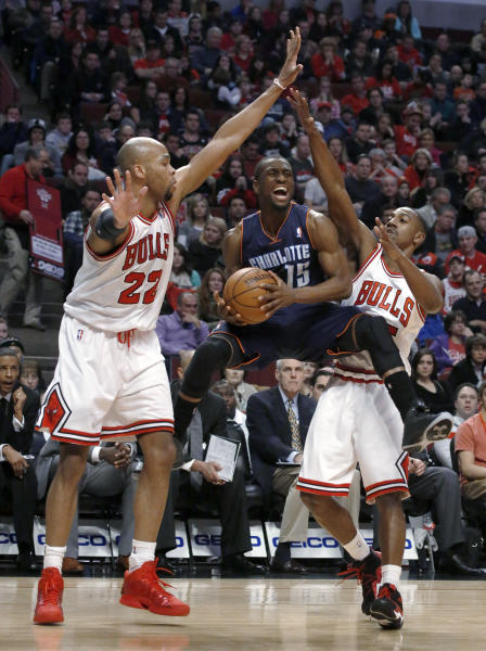 Charlotte Bobcats guard Kemba Walker (15) splits the defense of Chicago Bulls'Taj Gibson (22) and Marquis Teague during the first half of an NBA basketball game Monday, Dec. 31, 2012, in Chicago. (AP Photo/Charles Rex Arbogast)